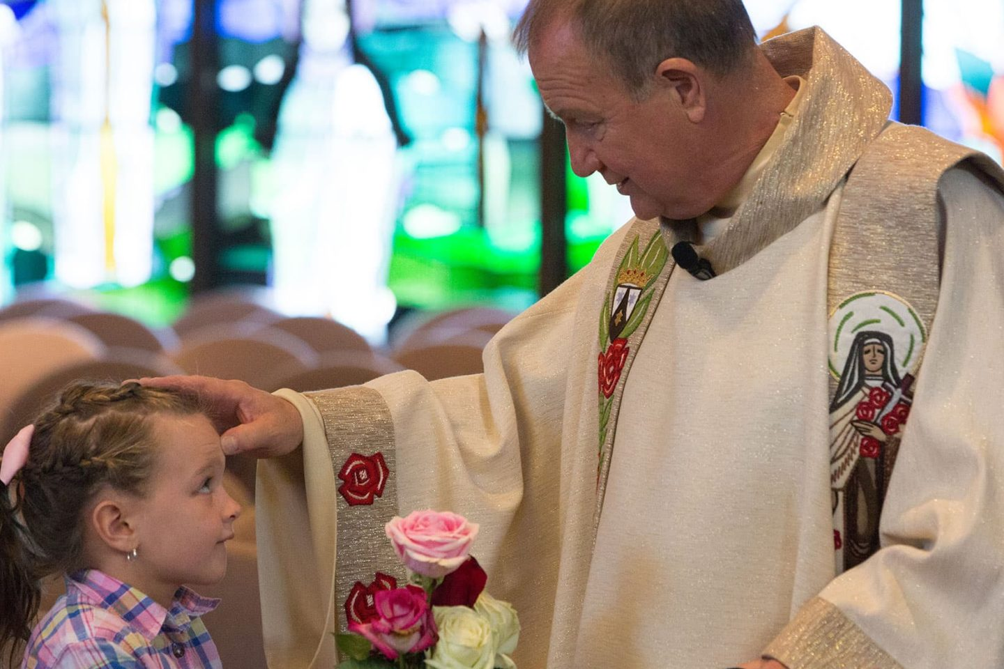 Fr. Bob Colaresi blesses young child at St. Therese Feast Day