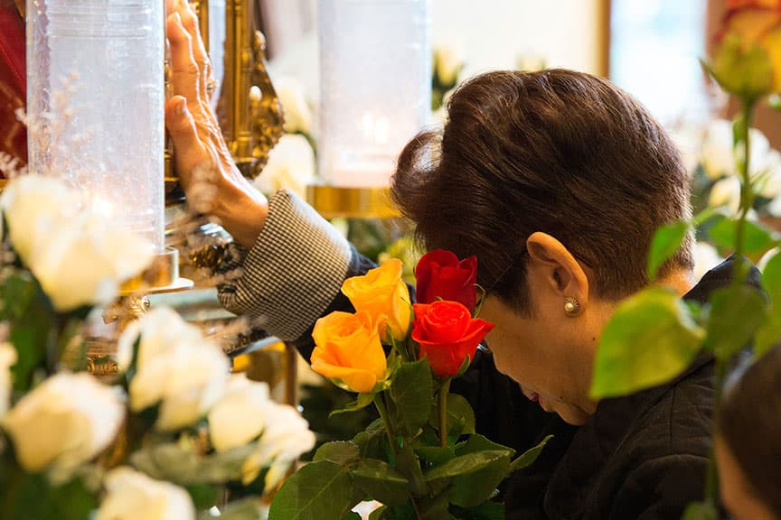 Woman venerating St. Therese's relics at Feast Day Celebration