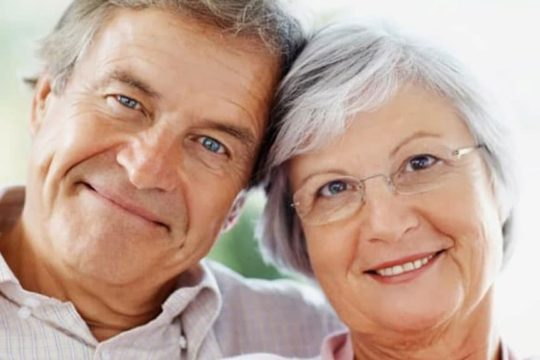 Older couple with heads touching, smiling at camera